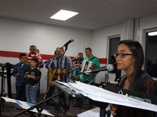 WNIN's Paola Marizan (far right) on Dec. 3 at Jasper Engines and Transmissions show, which raised money for Jasper Endows Today and Tomorrow. Grupo Guanacos, of Huntingburg, with all the members from El Salvador, performed behind her.