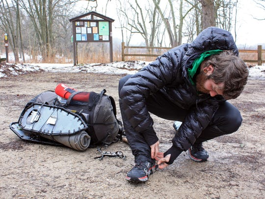 Mike Summers straps metal cleats to his shoes before continuing his trek on the Ice Age Trail at the start of the Eagle segment near Dousman.