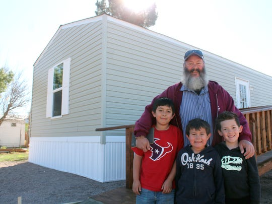 In this file photo, Haskell Hall, resident of Tularosa, stands with his grandsons Isaiah and Josiah Galban and their friend Tane Taiaroa in front of Hall's new home in Tularosa. The home is part of White Sands Habitat for Humanity's rehabilitation program and was made possible by help from the Otero County community.