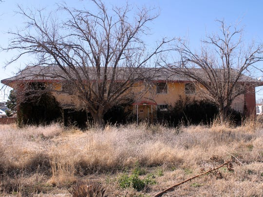 In this file photo, one of the Sahara Apartment buildings is covered in overgrown foliage.