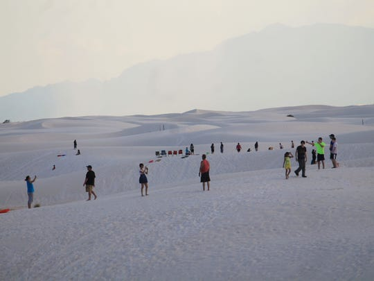 Visitors pose for photos on the gypsum dunes during