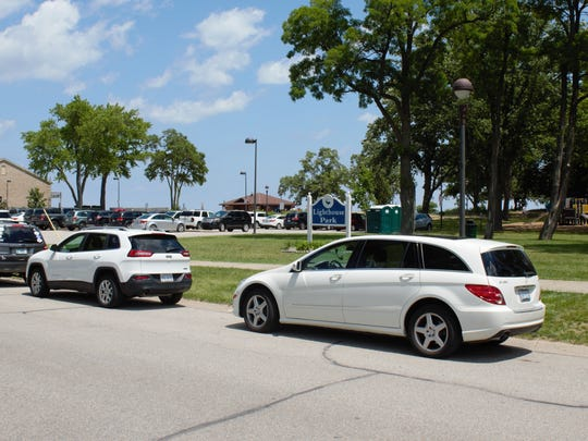 The parking lot and street fill with cars during the July 4 weekend. David Miller, who lives across the street from the park, said the street has been more crowded on the weekends than the lot since the parking fee was required.
