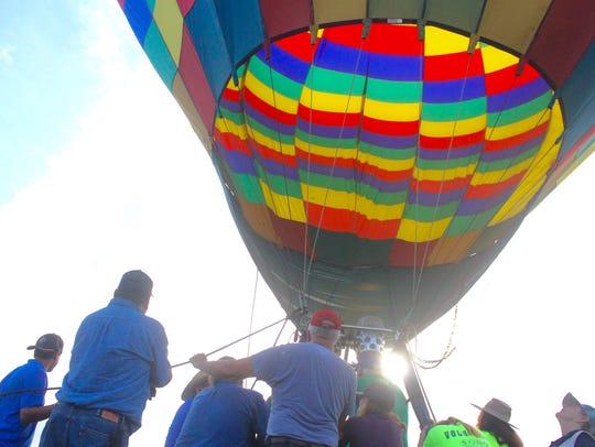 Crews get a hot air balloon prepared for flight at