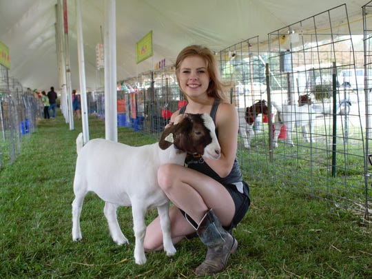 Hannah Buday, 15, poses with her goat, Moose. She said participating in the fair taught her responsibility and commitment.