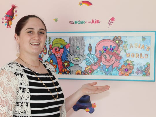 Sarah Williams with Jean Clark's artwork in De'Asia's