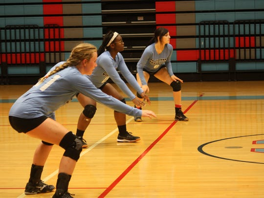 Grace Mills, Nikylah Long, and Lexi Smith get ready to dig the ball during Thursday nights game.