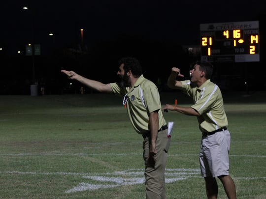Phoenix Day School for the Deaf head coach Dave Huber (left) and assistant coach Paul Amann (right) direct their players against Gilbert Arete Prep on Friday, Aug. 25, 2017 in Gilbert, Ariz.