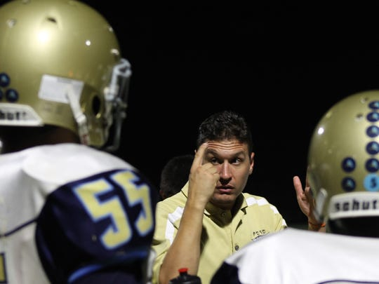 Phoenix Day School for the Deaf assistant coach Paul Amann talks to his team on the sidelines against Gilbert Arete Prep on Friday, Aug. 25, 2017 in Gilbert, Ariz.