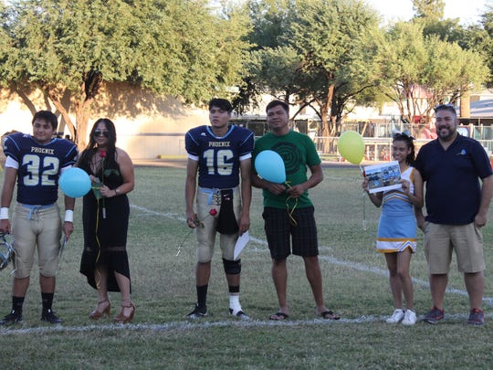 Cesar and Ernesto Aranda (middle) stand on the field during the ceremony to honor seniors at Phoenix Day School for the Deaf on Friday, Oct. 5, 2017 in Phoenix, Ariz. To the sides of them, Roger Bonilla (left) and cheerleader Yvette Nieto (right) are also honored.