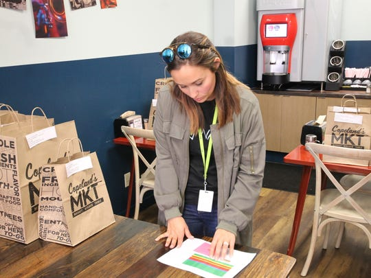 Whitney Savoie, Waitr's director of new market growth, sorts orders Monday at Copeland's MKT in Lafayette. More than 2,000 meals like these will be delivered to families in need this week as part of Waitr's Share Thanksgiving campaign.