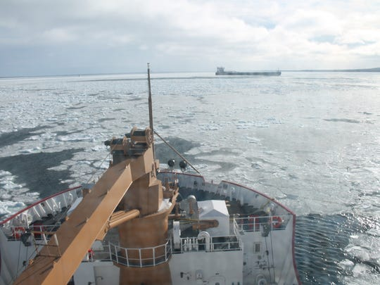 The crew of Coast Guard Cutter Mackinaw works to break
