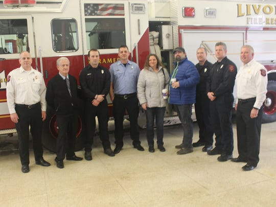 The Gebnars take a photo with fire department and city leadership March 7 at Livonia fire station 1.