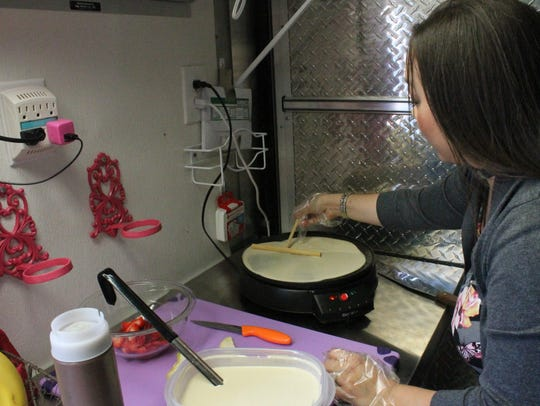 Michelle McCollum spreads crepe batter on a skillet