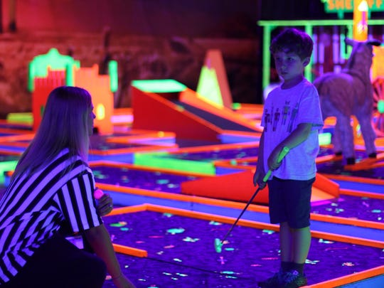 A junior golfer gets ready to tee off. The 18-hole blacklight mini golf course is a new attraction at Max Air Trampoline Park.