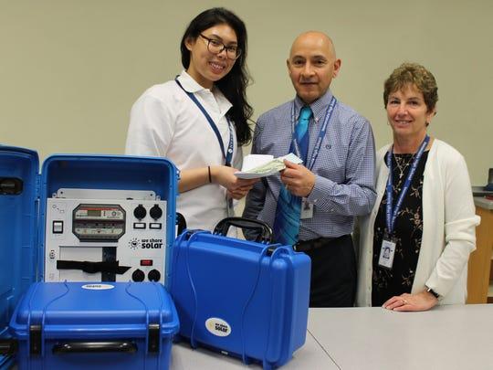 Ysobelle Reyes handsover her donation to the school's Solar Suitcase coordinators, Engineering teacher Al Kedersha and Campus Ministry Director Maureen Cote.
