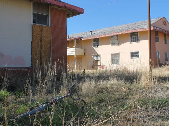 In this file photo, weeds grow through an abandoned bicycle on the property that houses the dilapidated Sahara Apartments.