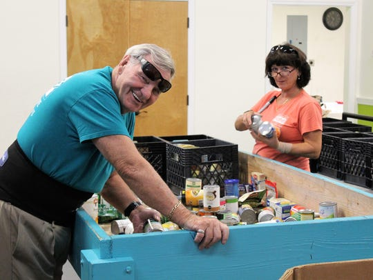 Volunteers Don Martin and Anna D'Amato sort food donated
