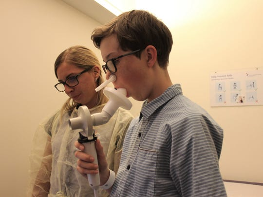 Ashley Aldhizer, right, tests Noah Colbert's lung function Wednesday at Colorado Children's Hospital. Noah has cystic fibrosis.