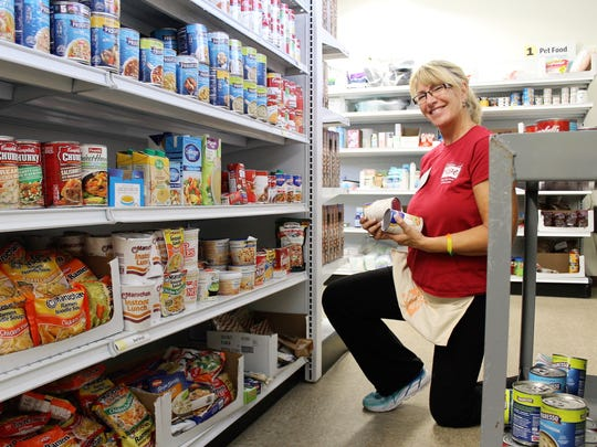House of Hope volunteer Julie Thyrring stocks the shelves