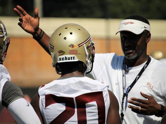 FSU head coach Willie Taggart talks with WR Keyshawn