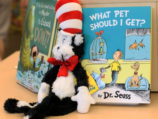 """A plush """"Cat in the Hat"""" toy is displayed next to """"What"""