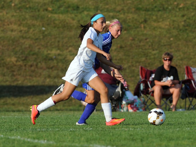 John Glenn's Ali Hill moves with the ball with Philo's Taylor Evans keeping pace.