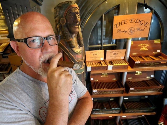 Mike LaMure, the owner of the Humidor stands next to a display of cigars in his shop on the square in Murfreesboro, on Thursday, August  14, 2014.