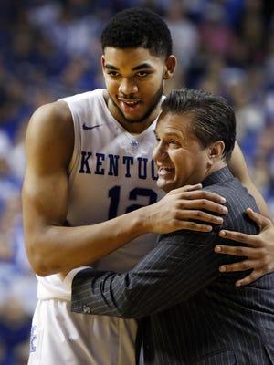 Kentucky's Karl-Anthony Towns, left, gets a hug from head coach John Calipari during the second half of an NCAA college basketball game against Georgia, Tuesday, Feb. 3, 2015, in Lexington, Ky. Kentucky won 69-58. (AP Photo/James Crisp)