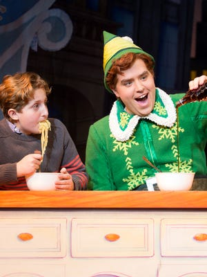 """Buddy the elf, played by Sam Hartley, pours syrup on his spaghetti in a memorable scene from """"Elf the Musical,"""" the Broadway version of the popular Christmas movie."""