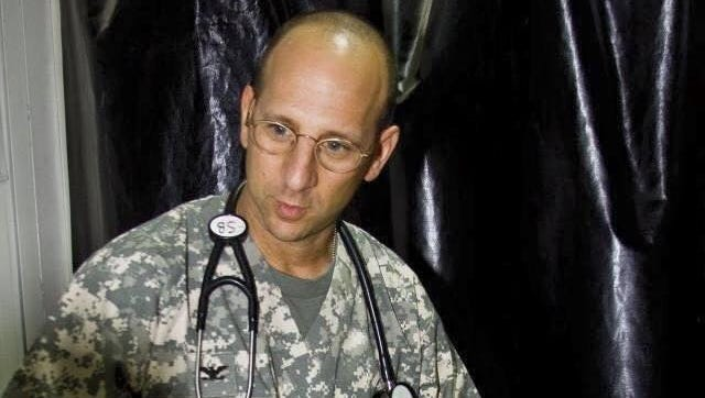 Army Col. Stephen Bernstein, MD, tuning fork in hand, treats a soldier in Iraq with a broken leg.