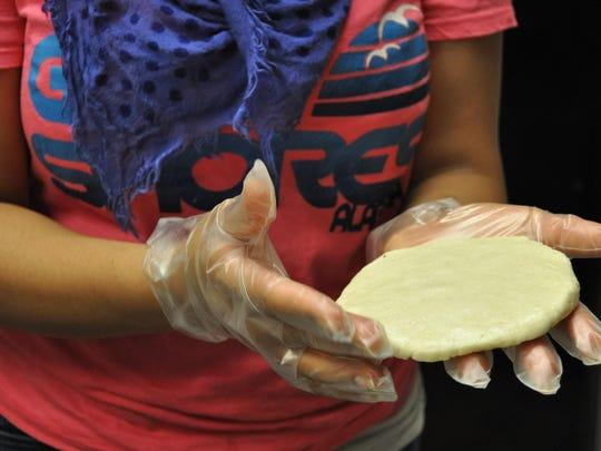 Carolina Francisco hand makes a gordita shell.