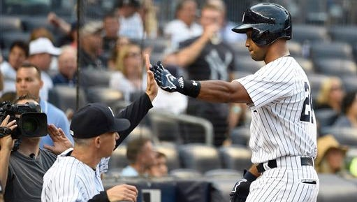 New York Yankees manager Joe Girardi greets Chris Young at the dugout after Young hit a solo home run off Seattle Mariners starting pitcher Mike Montgomery during the second inning of a baseball game at Yankee Stadium on Friday, July 17, 2015, in New York. (AP Photo/Kathy Kmonicek)