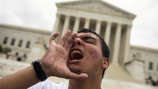 Gerson Quinteron of Washington yells during a demonstration on immigration at the Supreme Court in Washington, Thursday, June 23, 2016. A tie vote by the Supreme Court is blocking President Barack Obama's immigration plan that sought to shield millions living in the U.S. illegally from deportation. The justices' one-sentence opinion effectively kills the plan for the duration of Obama's presidency.