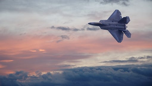 A F22 fighter jet flying through clouds in a colorful sky