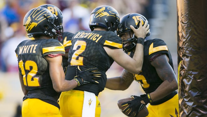 ASU quarterback Mike Bercovici (center) congratulates teammate wide receiver Devin Lucien after Lucien scored a touchdown against Washington during the fourth quarter of the college football game at Sun Devil Stadium in Tempe on Saturday, November 14, 2015.