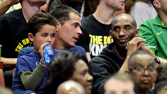 Rob Pelinka talks with Kobe Bryant during the NCAA men's basketball tournament West Regional final at Honda Center on March 26, 2016 in Anaheim, California.