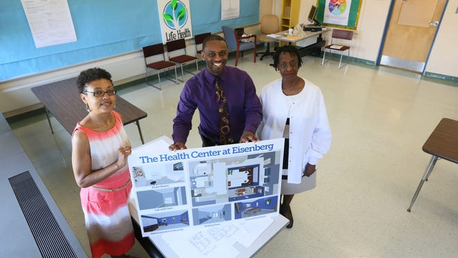 Left to right Nanci Woodson, case manager for behavioral health,  Forrest Watson, administrator for Life Health, Sandra Jackson, nurse practitioner, with a rendering of what the room they are currently working will look like when completed in the future. Eisenberg Elementary School will soon have a wellness center available for students and families.
