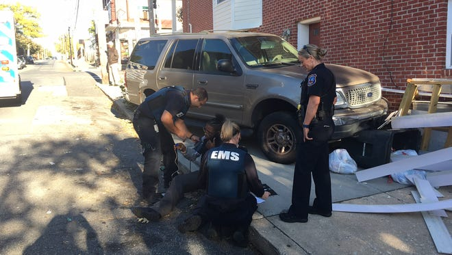Emergency responders treat a man following a crash in the 1300 block Chestnut St., Wilmington.