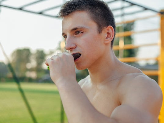 Man is eating carbohydrate bar during workout. Outdoor gym backg
