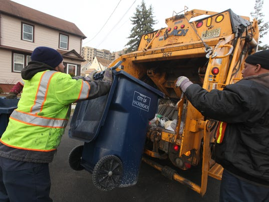 Hackensack garbage pickup has been increased to twice a week from once a week. Here sanitation workers collect garbage in teh morning on Stanley Pl. and Haynes St.