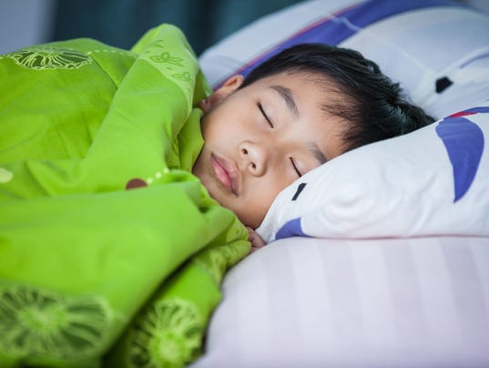 Healthy child. Little asian boy sleeping peacefully on bed.