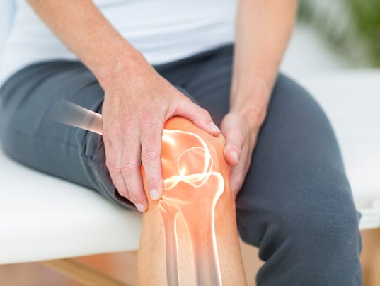 Mid section of man suffering with knee cramp