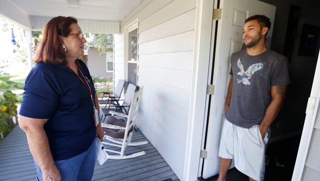 Cassandra Siperko with the Springfield-Greene County Health Department talks with Aaron Loudermill on his front porch, informing him of services the health department offers, on Thursday, Aug. 4, 2016.