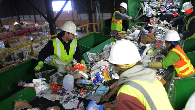Workers sort though recyclables at Garten Material Recovery Facility on Friday, January 9, 2015, in Salem.