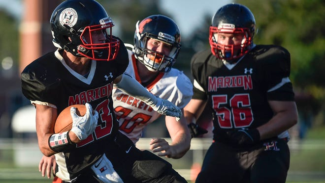 Marion Harding's Bryce Starner shoots a glance to his side as he takes the ball downfield during the Marion Harding versus Mount Vernon football game on Friday night.