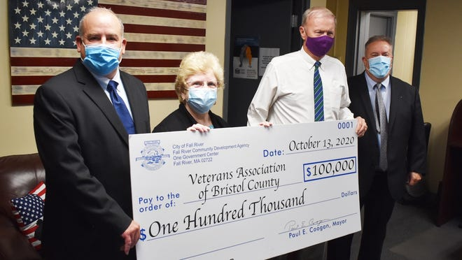 From left, Jim St. Laurent, executive director, Veterans Association of Bristol County, board member Kathy Splinter, Fall River Mayor Paul Coogan and Michael Dion, executive director Community Development Agency hold the check representing funds that will be used to help veterans obtain jobs at an event Tuesday in Fall River.
