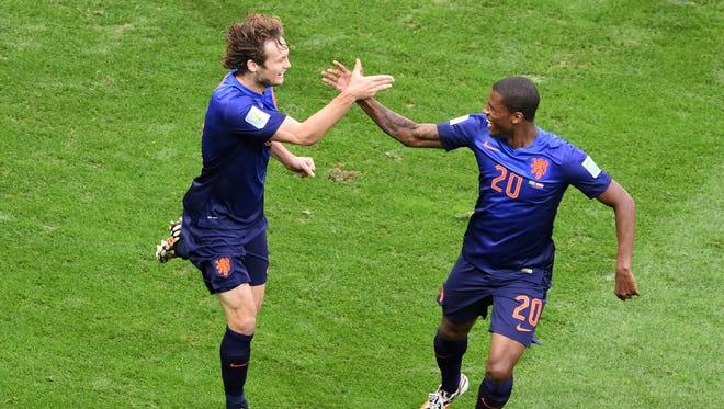 Netherlands' defender Daley Blind (L) celebrates with is teammate Netherlands' midfielder Georginio Wijnaldum after scoring a goal.