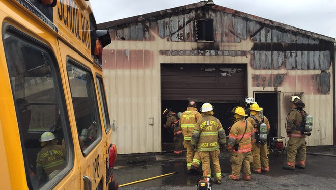 Firefighters work at the scene of a fire at Wapahani High School Wednesday afternoon.