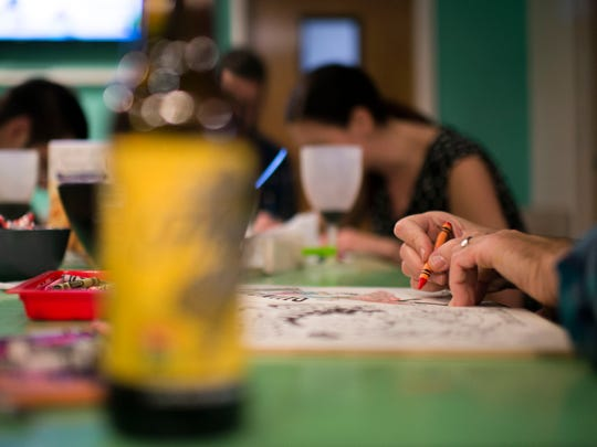 Owner Jim McHugh wields a crayon as McArt a la Carte hosts an adult coloring night complete with snacks and beer in Woodbury.