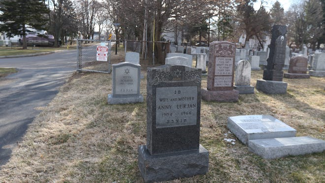 Some visitors and family members buried at Waad Hakalel Cemetery in Rochester react to the damage to gravestones.   One headstone, on the ground, is near an entrance to the cemetery at Chesterfield Drive.